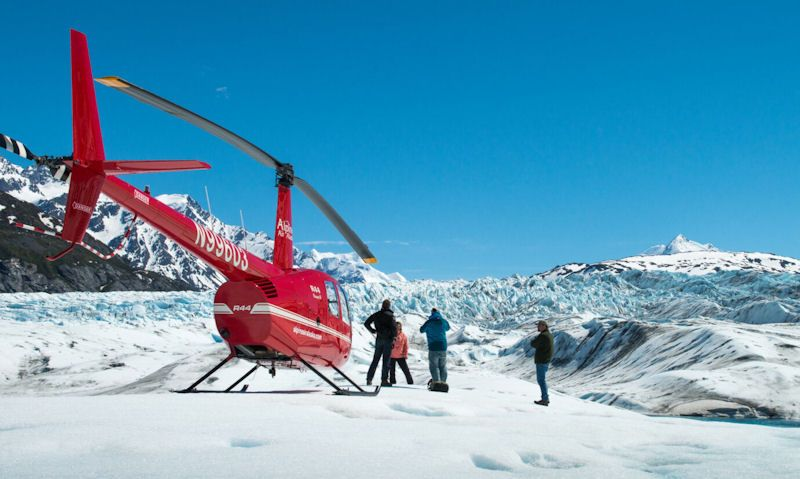 Passengers watch on with Robinson R44 helicopter landed on glacier