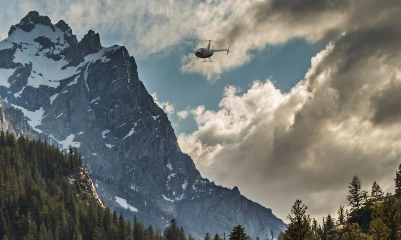 Robinson R44 seen flying near to snow capped mountain