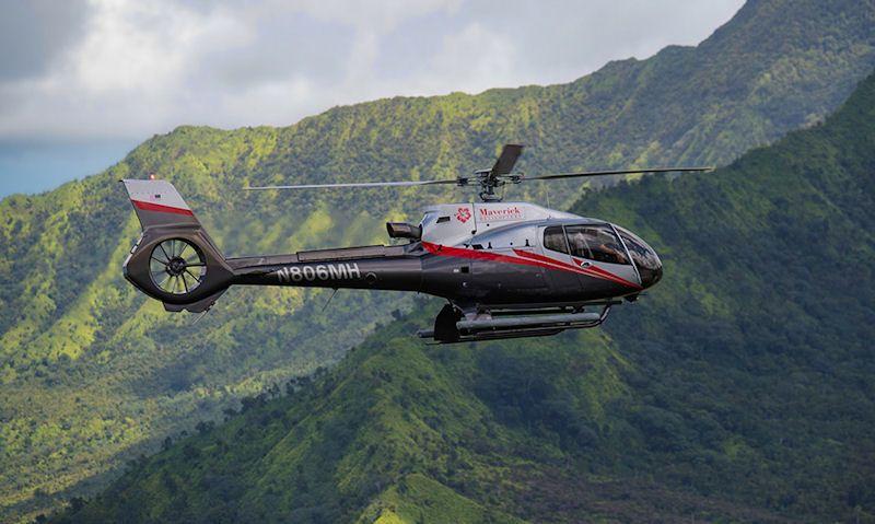 Maverick Helicopters' Airbus EC130 soaring above Kauai rainforest