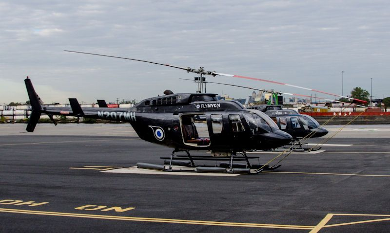 FlyNyon helicopters sat on helipad awaiting passengers