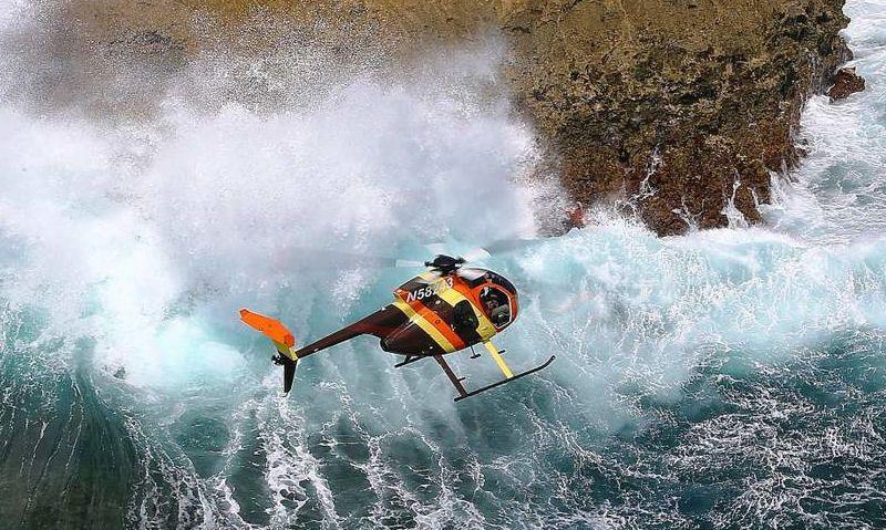 Magnum PI Hughes 500 Soaring above crushing waves on coastline