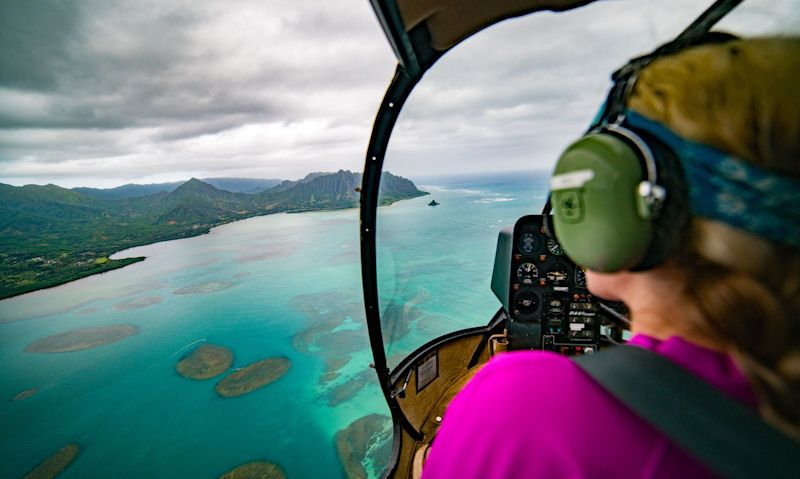 Female sitting in co-pilot seat looking over to Oahu's clear water with coral reef
