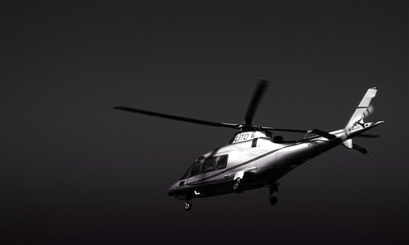 Chartered helicopter in sky, black image