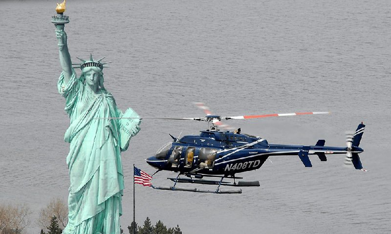 Bell 407 passing by Liberty Island in mid flight