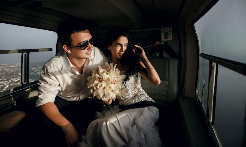 Bride and groom in helicopter cabin in flight