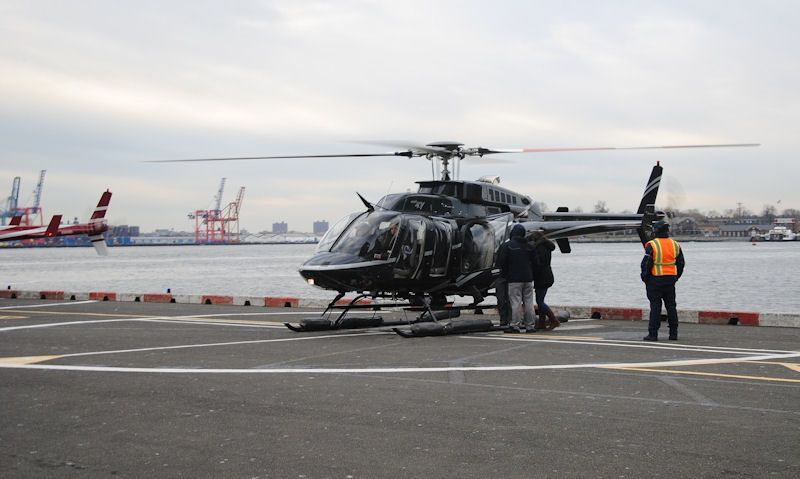 HeliNY Bell 407 on Pier 6 heliport watched on by ground crew member