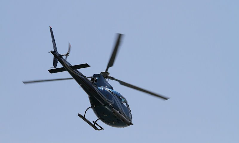Airbus H125 helicopter seen in flight, clear blue sky