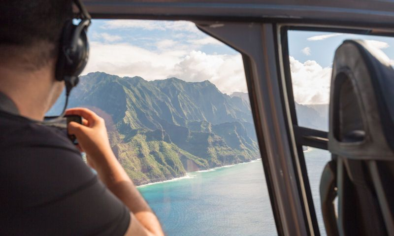 Helicopter tour passenger photograhing Na Pali Coast using mobile or cellphone