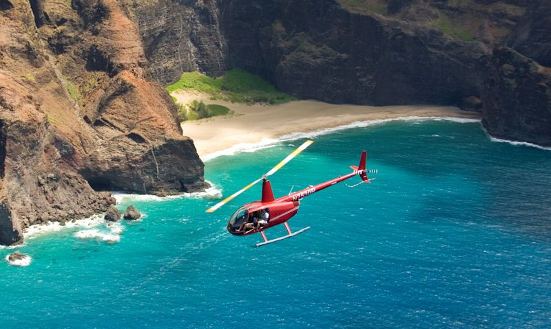 Robinson R44 helicopter viewing waterfall with tourists onboard