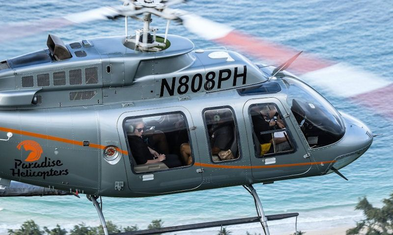 Passengers seen inside Paradise Helicopters Bell 407 in flight