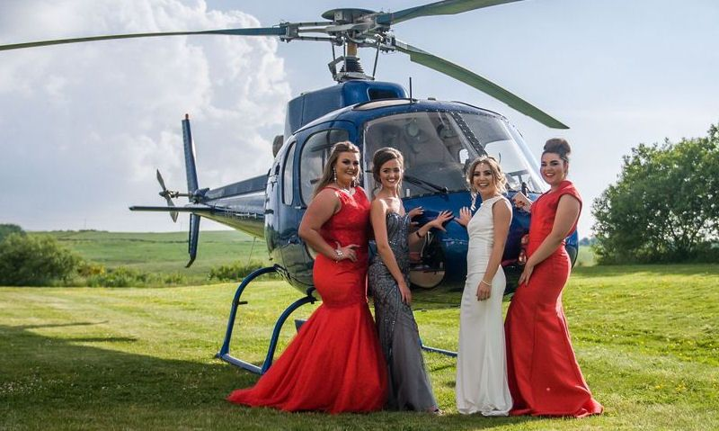 Group of school prom girls pose next to helicopter