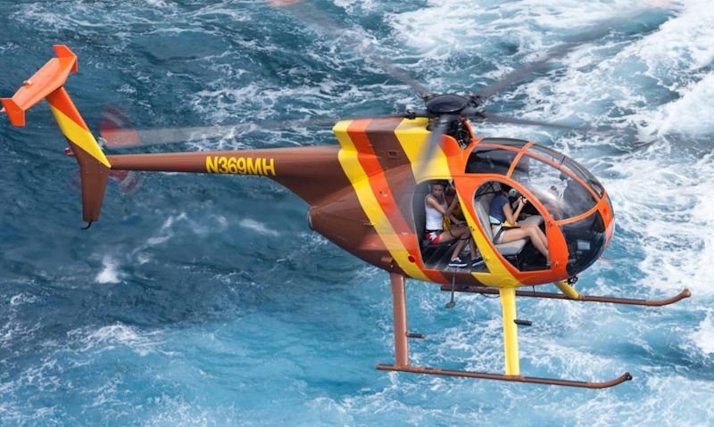 Magnum Helicopters open door MD 500D type over the ocean