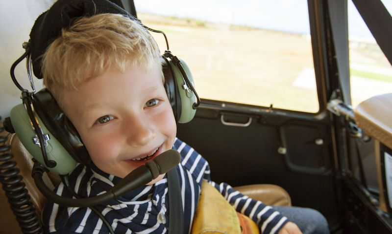 Happy child wearing headset inside Robinson R44 helicopter