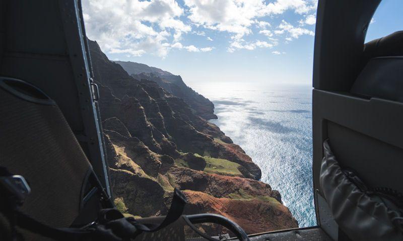 Na Pali Coast seen through an open door of Jack Harter Hughes 500 helicopter