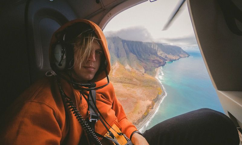 Man poses for picture in flight with Kauai coastline seen in background