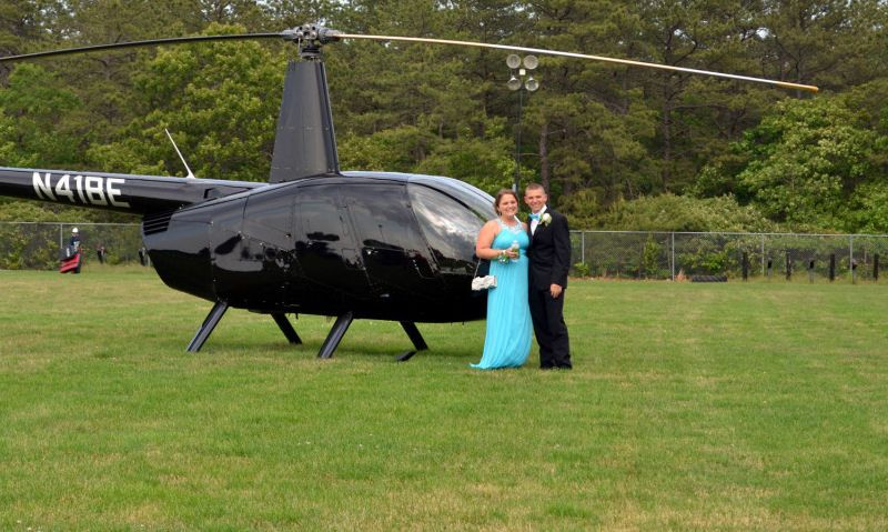 Prom dates posing next to Robinson R44 helicopter on school field