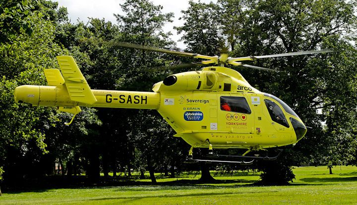 Great North Air Ambulance helicopter ascending off grass meadow